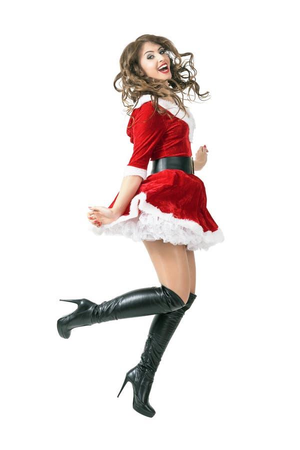 跳跃在空中的快乐的圣诞老人女孩 免版税库存照片