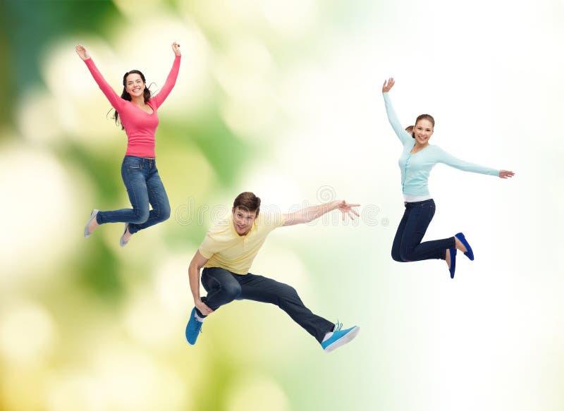 跳跃在空气的小组微笑的少年 免版税库存照片