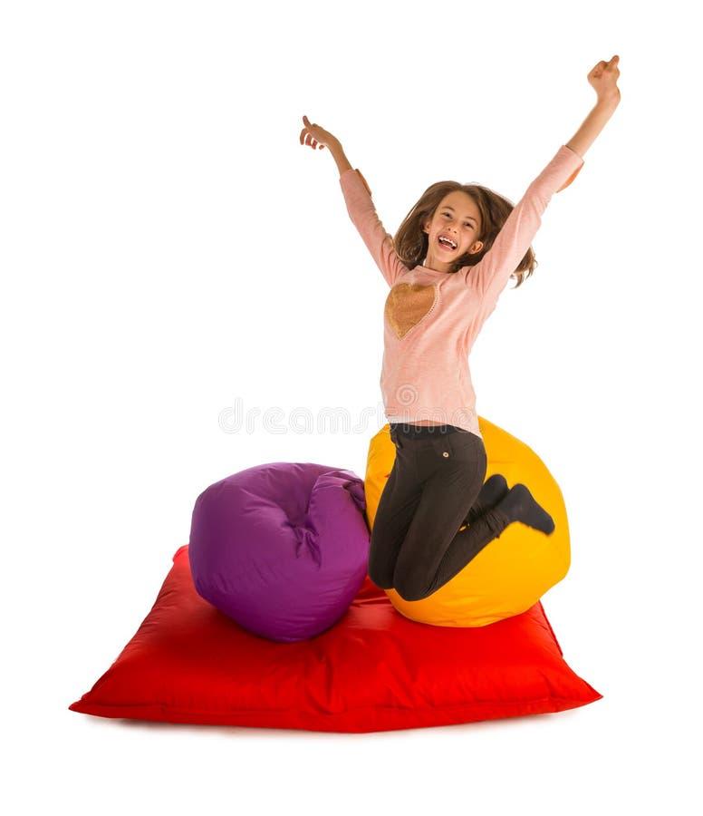 跳跃在装豆子小布袋椅子和装豆子小布袋沙发附近的愉快的女孩 图库摄影