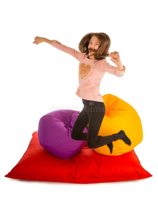 跳跃在装豆子小布袋椅子和装豆子小布袋沙发附近的滑稽的女孩 库存图片