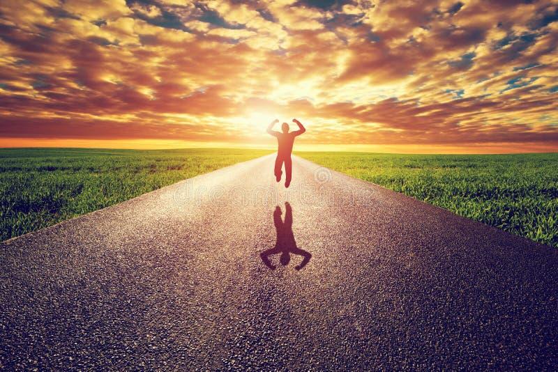 跳跃在长的直路,往日落太阳的方式的愉快的人 免版税库存图片