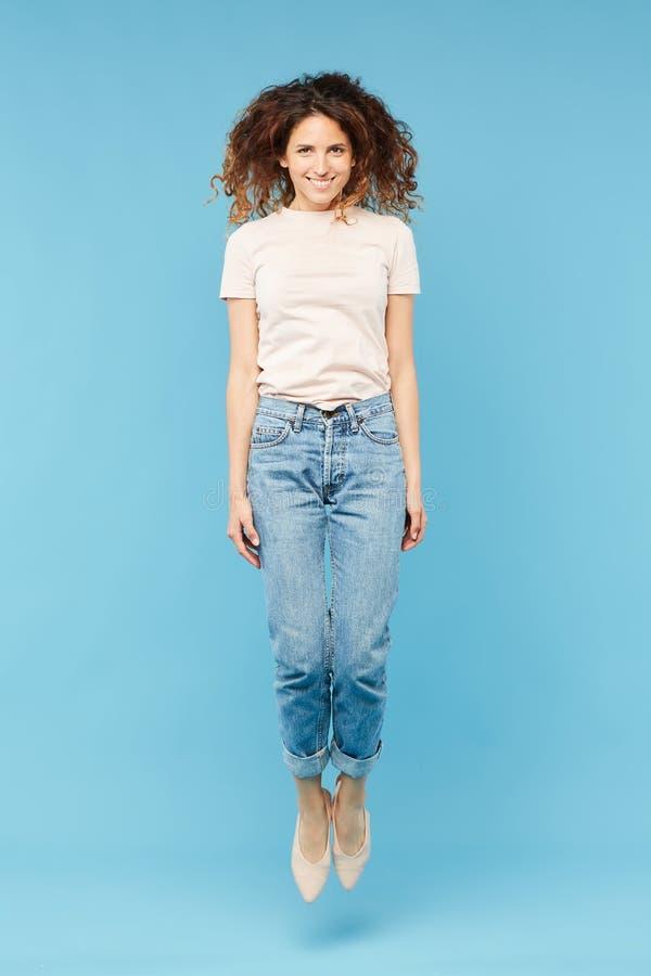 跳跃在隔离的牛仔裤和T恤杉的愉快的年轻偶然女性 图库摄影
