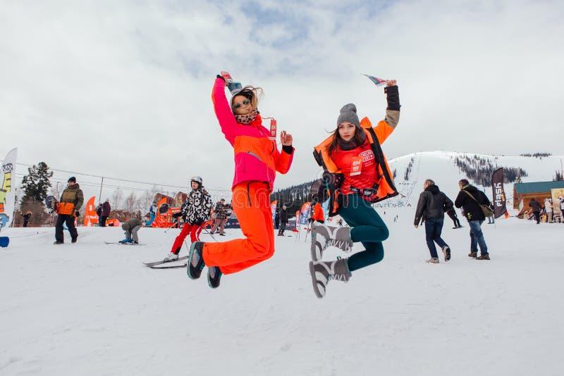 跳跃在雪倾斜的两个女孩 库存图片