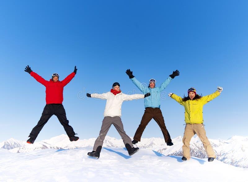 跳跃在雪和享受冬天的青年人 免版税库存照片