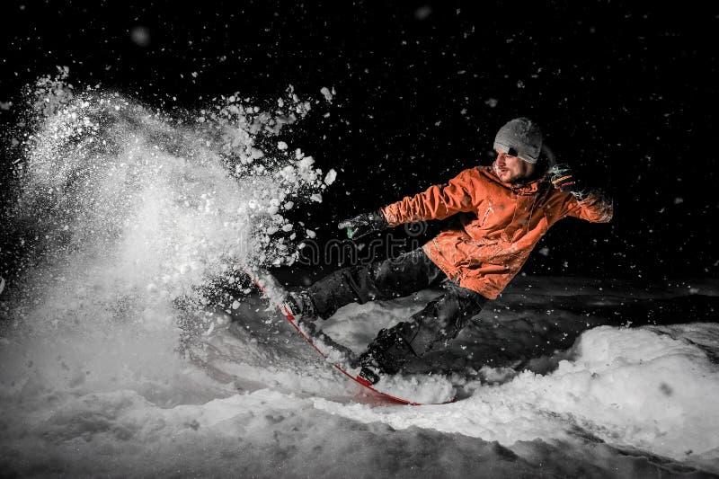 跳跃在雪的年轻freeride挡雪板在晚上 库存图片