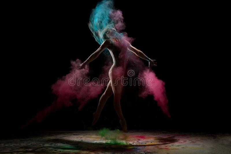 跳跃在颜色在黑暗的尘云的亭亭玉立的女孩 免版税库存照片
