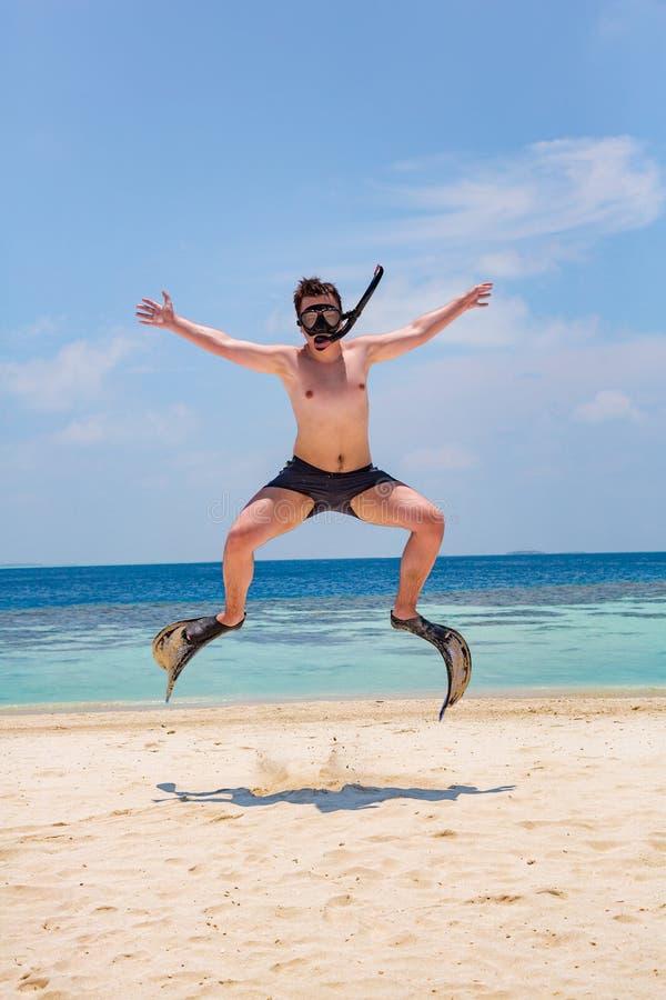 跳跃在鸭脚板和面具的滑稽的人 库存图片