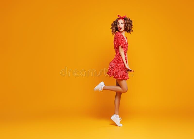 跳跃在黄色背景的红色夏天礼服的概念愉快的情感年轻女人 库存照片