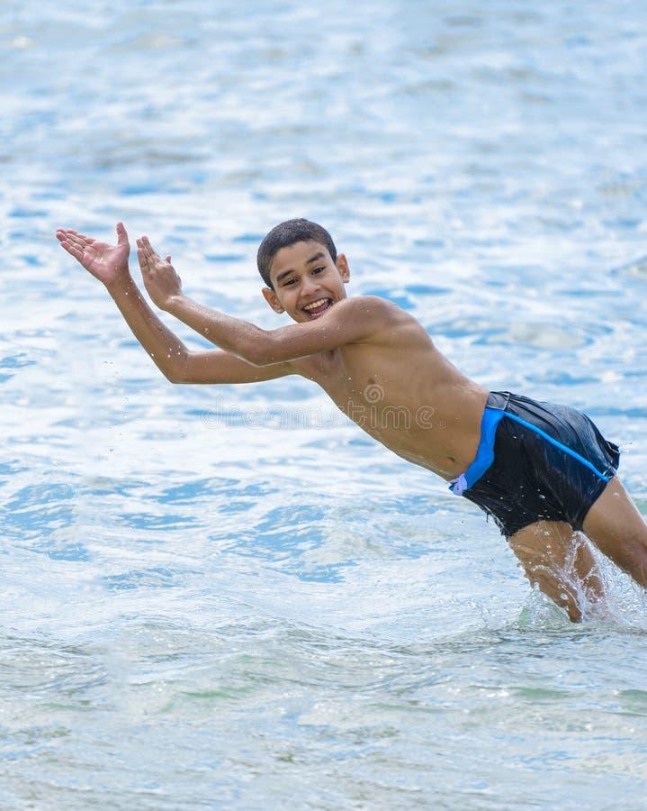 跳跃在水中的活跃愉快的男孩 免版税库存照片