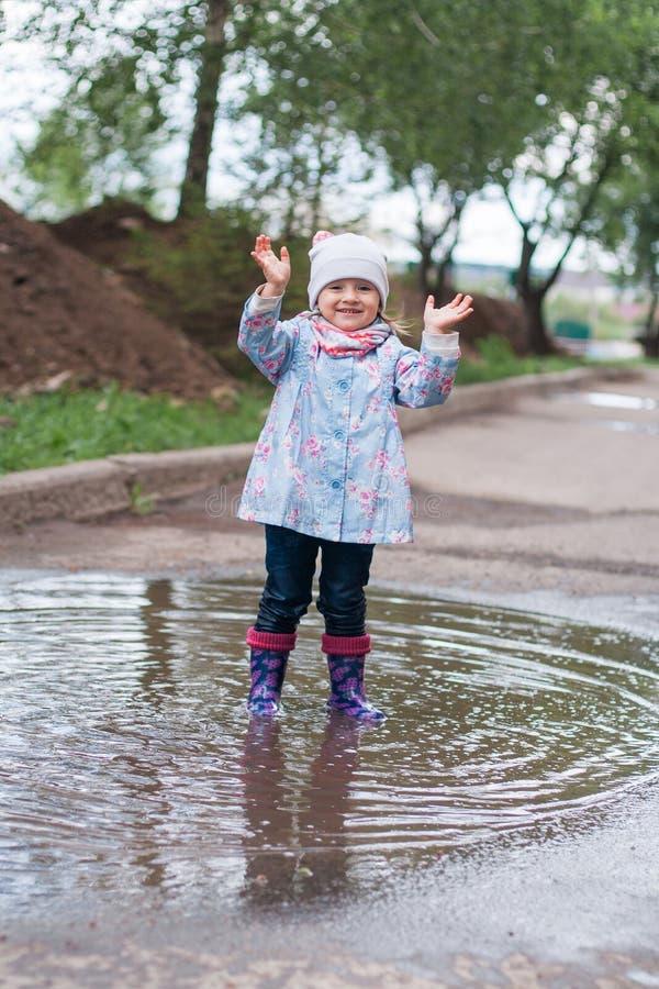 跳跃在水坑的小女孩 图库摄影