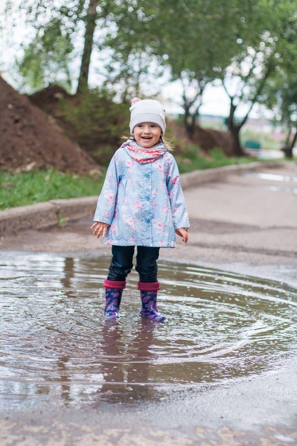 跳跃在水坑的小女孩 免版税库存照片