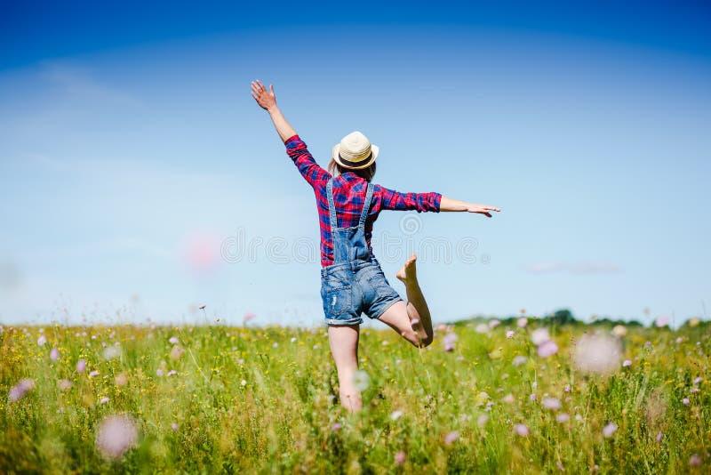 跳跃在绿色领域的帽子的愉快的妇女反对蓝天 免版税图库摄影