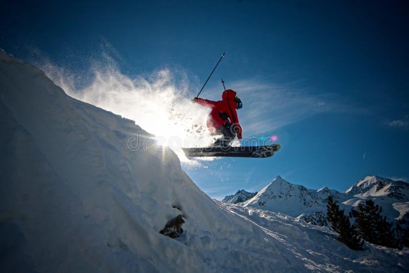 跳跃峭壁的极端滑雪者 免版税图库摄影