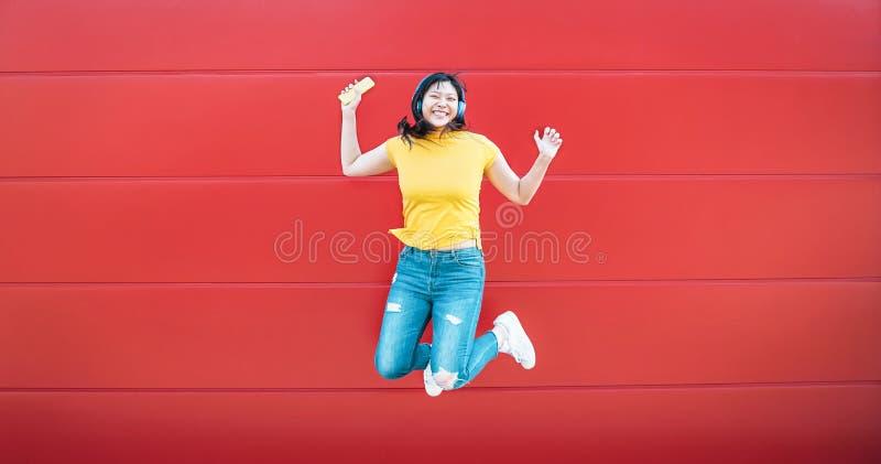 跳跃愉快的亚裔的女孩,当室外听的音乐-获得疯狂的中国的妇女跳舞歌曲的乐趣反对红色背景时 库存照片