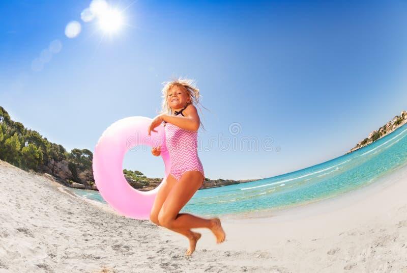 跳跃愉快的女孩度过假期在海滩上 库存照片