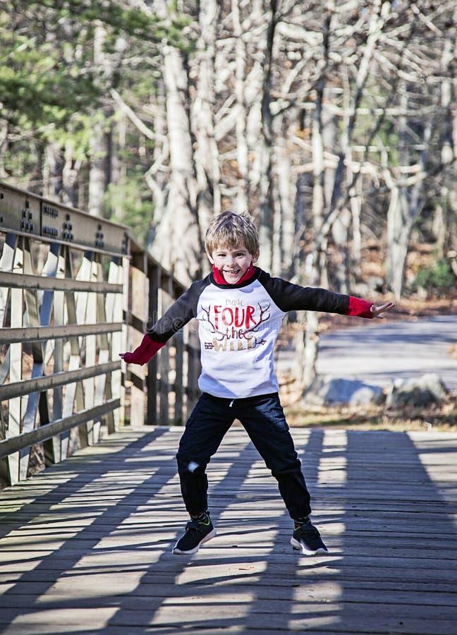 跳跃愉快的男孩使用和外面 免版税图库摄影