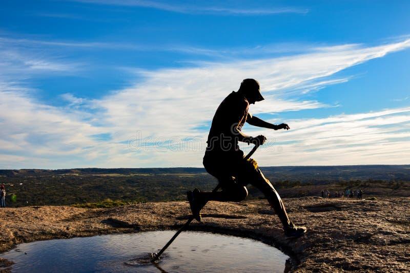 跳跃水坑的剪影 免版税库存图片
