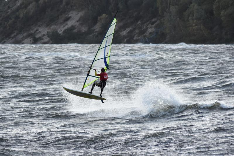 跳跃的匿名风帆冲浪者在波罗的海风雨如磐的水域中 库存图片