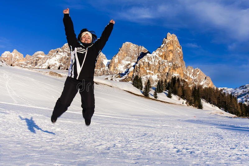 跳跃的妇女雪山幸福假期 免版税库存图片