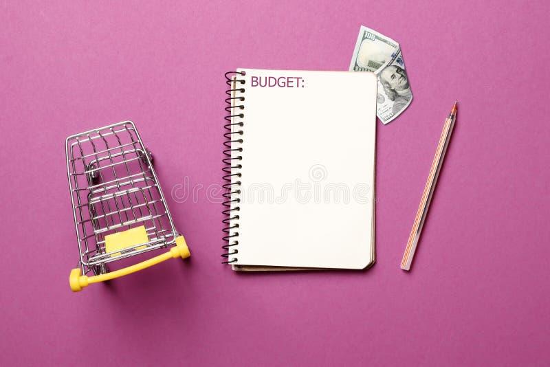跳跃的推车,有笔的白纸笔记本在桃红色背景 免版税库存图片