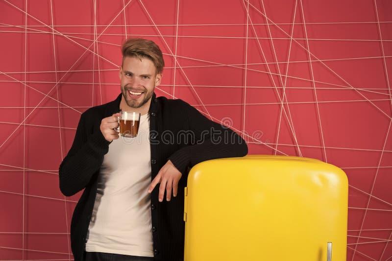 跳跃的早晨茶开始您的天 与早晨饮料的人快乐的微笑在冰箱附近 学士举行茶 库存照片