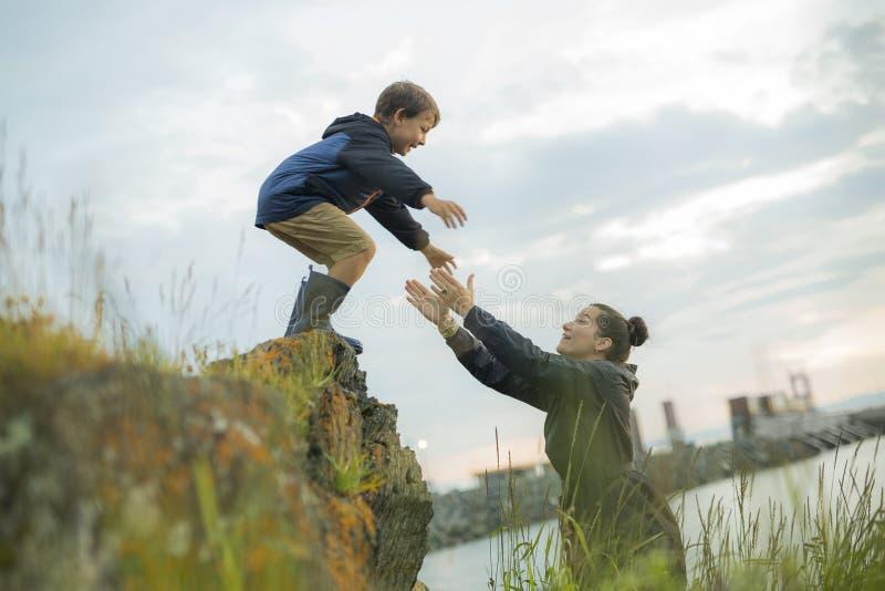 跳跃的母亲帮助的孩子岩石 免版税库存照片