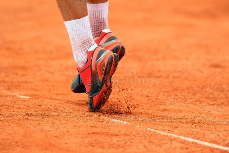 跳跃的网球员的脚服务在黏土网球场 库存照片