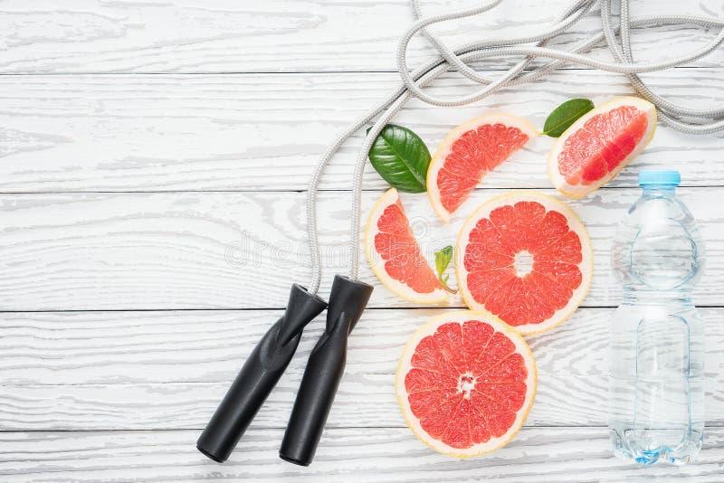 跳跃绳索、新鲜的葡萄柚和瓶水,在土气白色木桌上,顶视图,平的位置,健身辅助部件 免版税库存图片