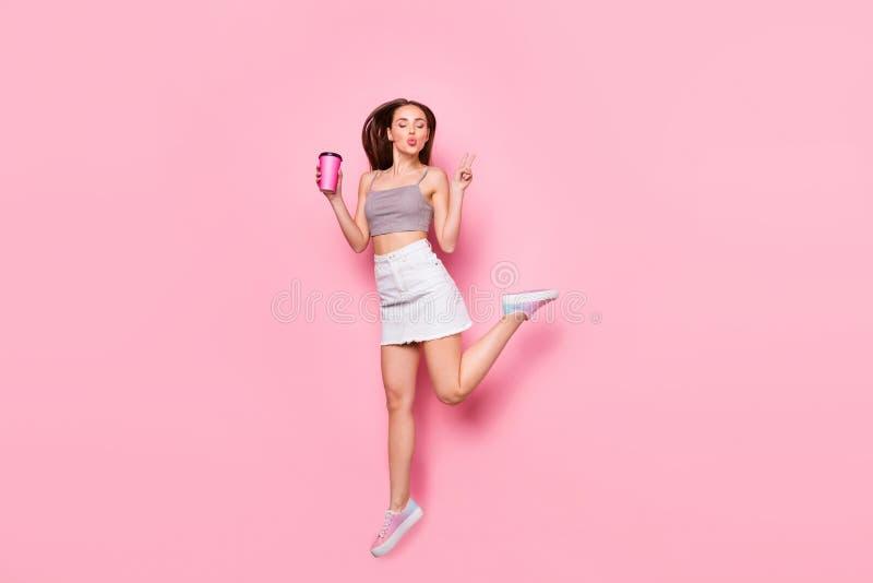 跳跃逗人喜爱的青年时期全长的照片做拿着杯子用热的饮料的v标志送空气亲吻被隔绝  免版税库存图片