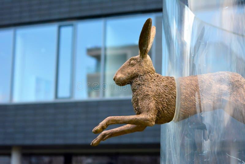 跳跃通过玻璃箍的一只古铜色兔子的雕塑由艺术家萨布里纳Hohmann 免版税库存照片
