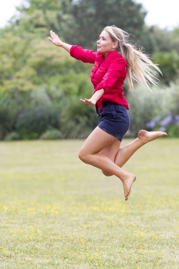 跳跃高与乐趣的激动的20s妇女在晴朗的公园 库存照片