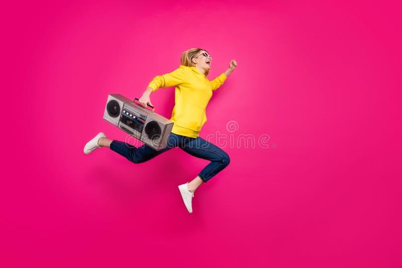 跳跃高冲的疯狂的夫人充分的身体照片到学生党穿戴偶然成套装备被隔绝的桃红色背景 免版税图库摄影