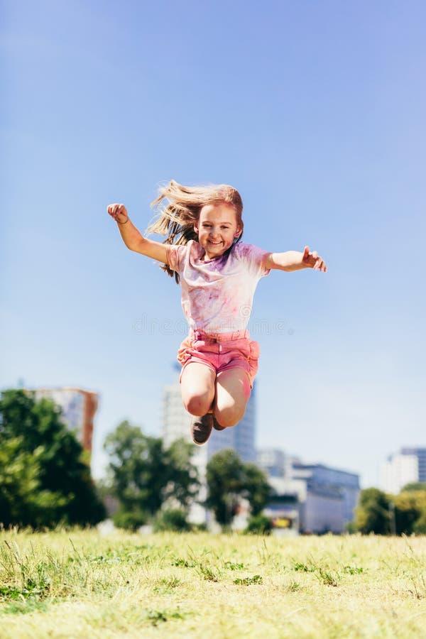 跳跃高在五颜六色的肮脏的衣裳的城市公园的小女孩 免版税库存图片