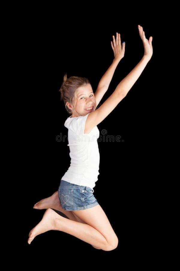 跳跃高在喜悦和高兴的白色T恤杉和demin短裤的少女 免版税库存图片