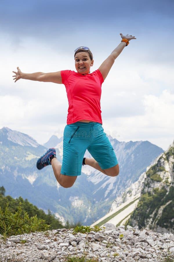 跳跃高在幸福的年轻俏丽的妇女,在山 免版税库存照片