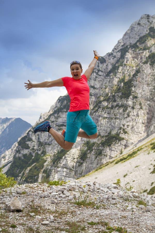 跳跃高在幸福的年轻俏丽的妇女,在山 库存照片