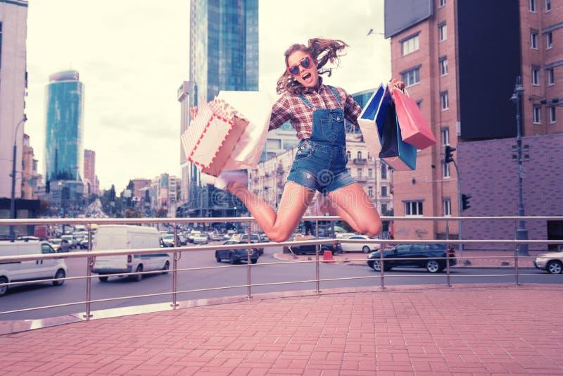 跳跃高在惊人的购物天以后的时髦的情感妇女 免版税图库摄影