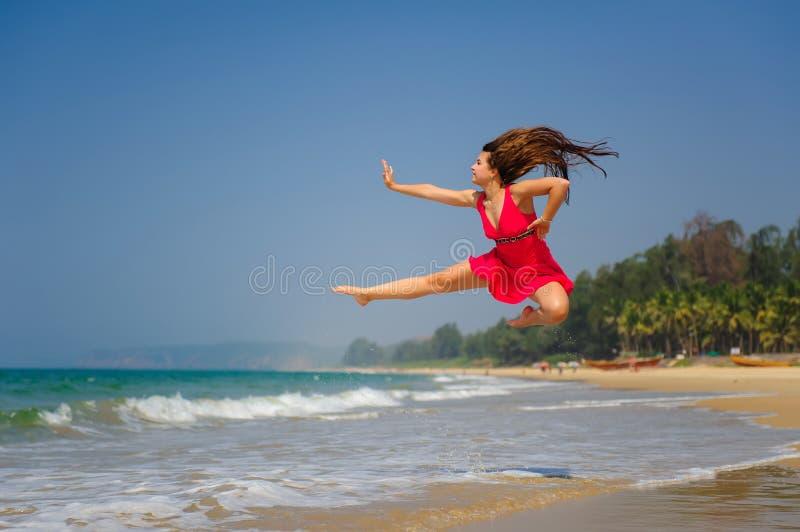 跳跃高在湿沙子上的愉快的年轻白种人妇女在热带海在好日子 赤足,短的红色礼服的一个运动的女孩 图库摄影
