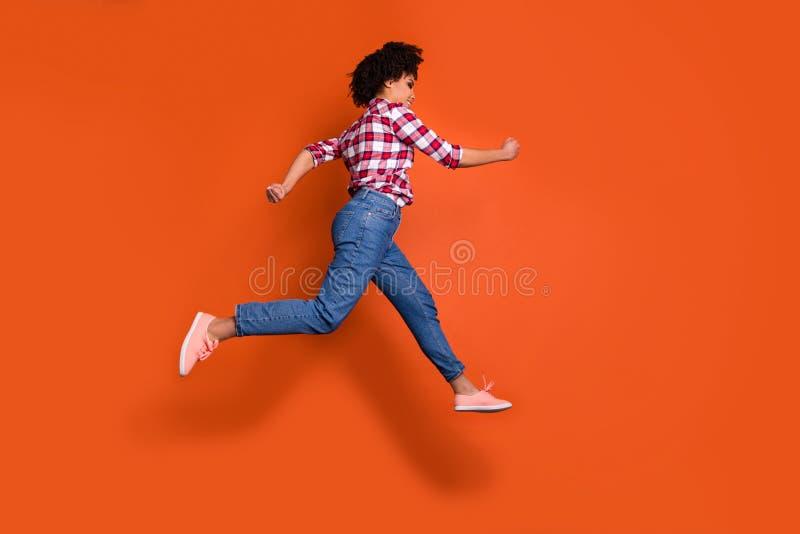 跳跃高运动夫人奔跑购物的销售折扣全长旁边照片穿牛仔裤牛仔布裤子格子衬衫 库存图片