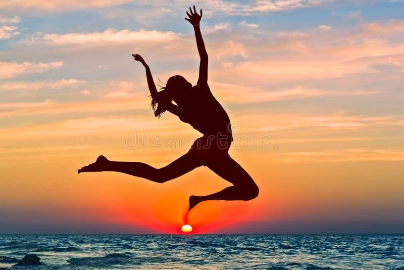 跳过海的女孩的剪影在日落 图库摄影