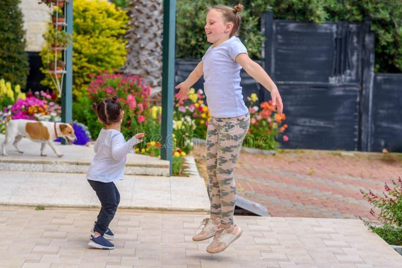 跳过自然背景的可爱,嬉戏,快乐,愉快的可笑的夫妇孩子全长画象  库存照片