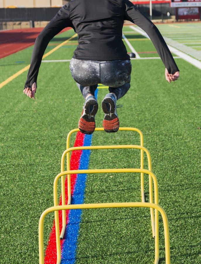 跳过训练障碍的女运动员从后面 库存照片