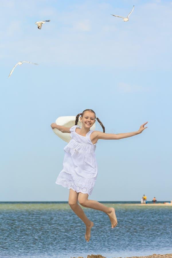 跳过水的快乐的女孩在海滩 图库摄影