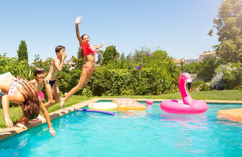 跳进游泳场的愉快的孩子 免版税库存照片