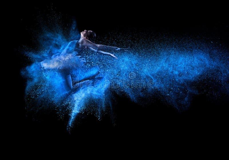跳进蓝色粉末云彩的年轻美丽的舞蹈家 库存图片