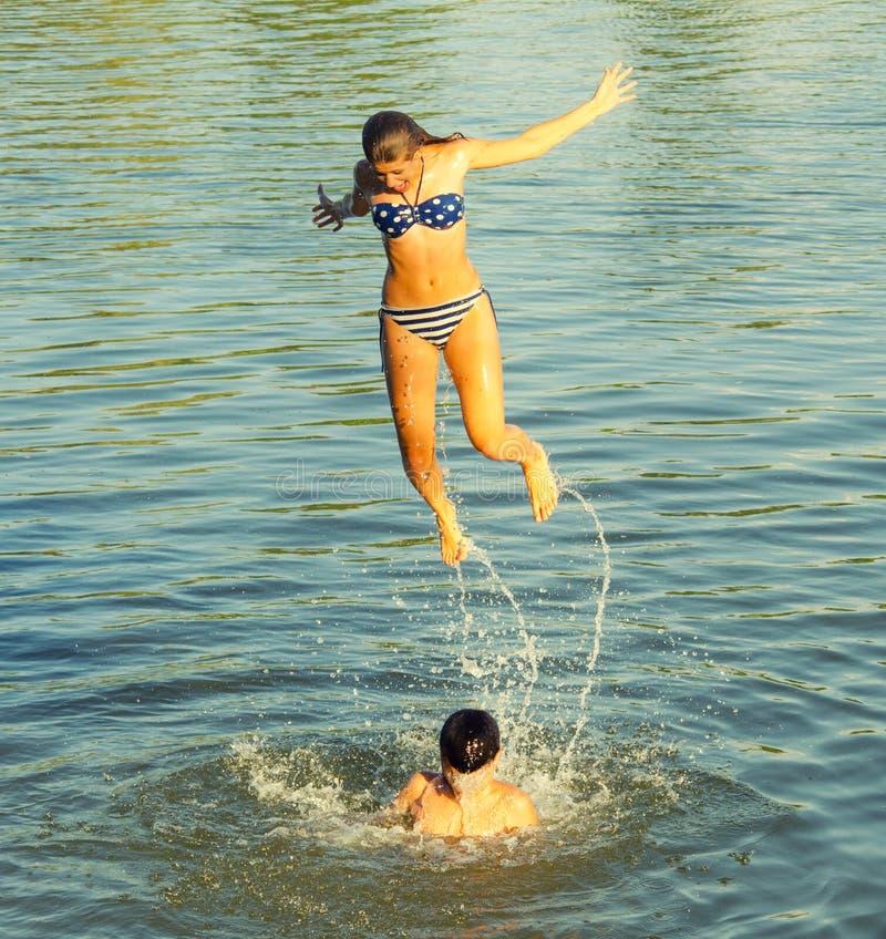 跳进从男孩的河的十几岁的女孩担负 免版税库存照片
