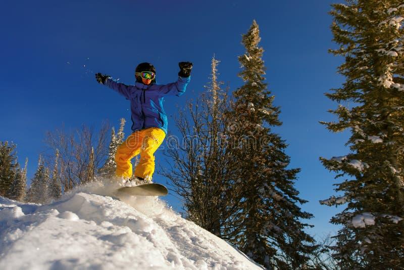 跳通过与深蓝天的空气的挡雪板在背景中 库存图片