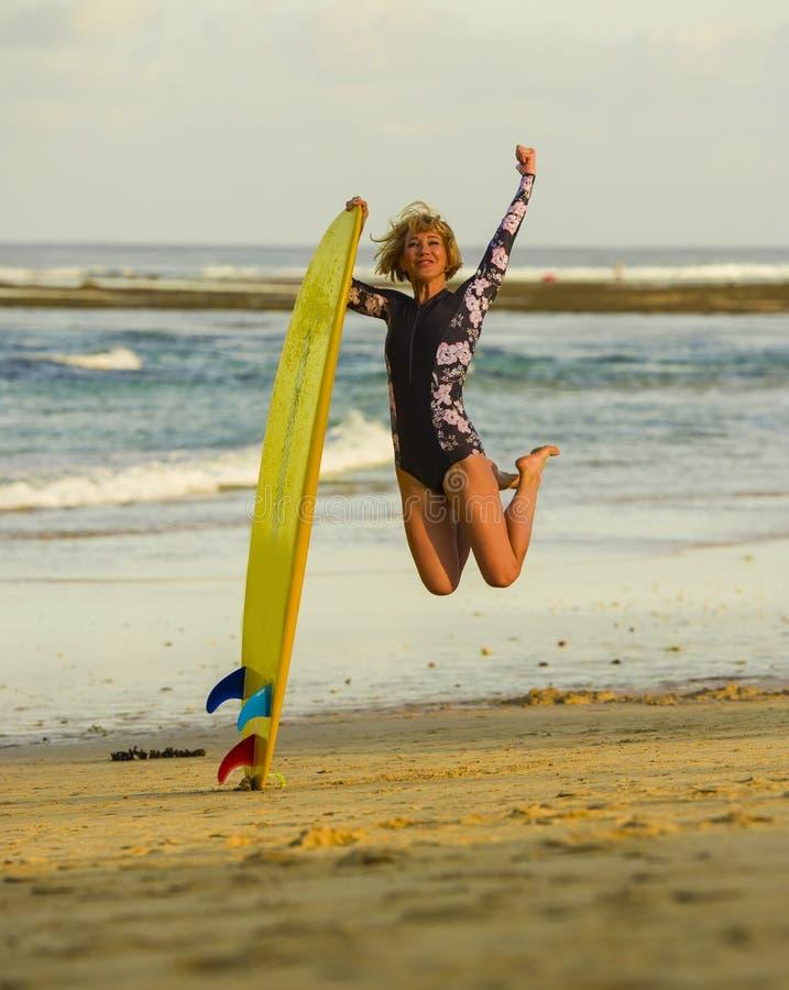 跳高在天空中的年轻愉快和可爱的冲浪者女孩拿着水橇板在冲浪在美丽的热带海滩前享用 免版税库存图片