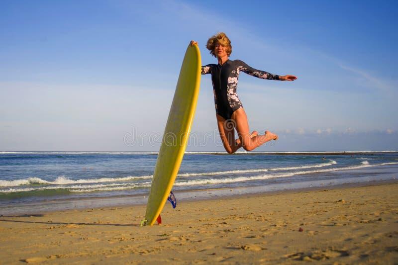 跳高在天空中的年轻愉快和可爱的冲浪者女孩拿着水橇板在冲浪在美丽的热带海滩前享用 免版税图库摄影