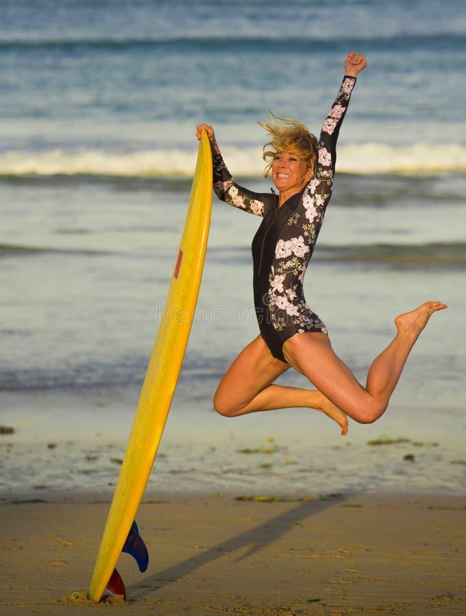 跳高在天空中的年轻愉快和可爱的冲浪者女孩拿着水橇板在冲浪在美丽的热带海滩前享用 库存照片